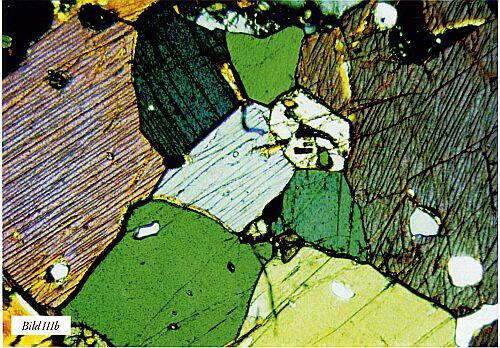 """Bild III. Två """"basiska"""" bergarter, a) diabas med väl inväxta mineral och b) amfibolit som bildats genom omkristallisation och har fått en mycket """"lucker"""" textur som ger dåliga mekaniska egenskaper. Tunnslip. Förstoringar ca 100 gånger resp. 50 gånger, polariserat ljus."""